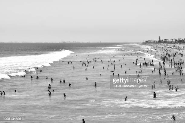group of people swimming in sea against sky - orange county crowded beaches stock pictures, royalty-free photos & images