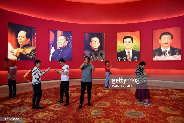 Group of people take pictures in front of portraits of late Chinese chairman Mao Zedong and former Chinese leaders Deng Xiaoping, Jiang Zemin, Hu...