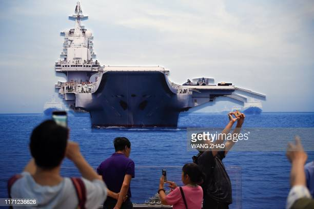A group of people take pictures of a model of the aircraft carrier Liaoning at an exhibition marking China's achievements over the past 70 years...