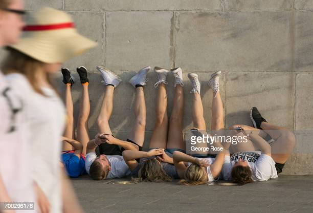 A group of people take pictures of their feet while on their backs looking up from the base of the Washington Monument on June 4 2017 in Washington...