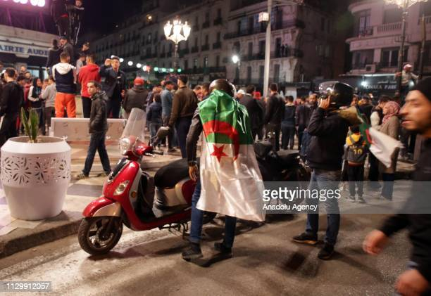 A group of people take the street to celebrate after Algerias President Abdelaziz Bouteflika postponed the April presidential election and withdrew...