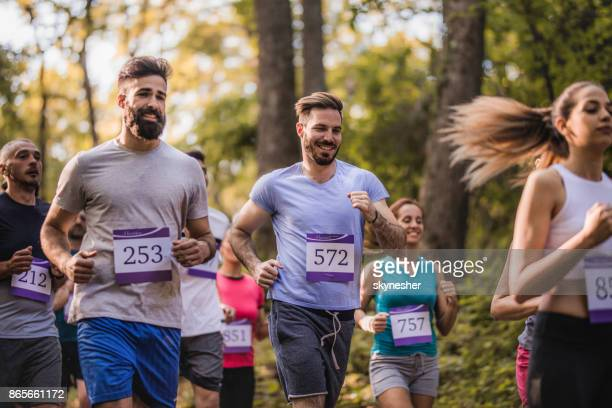 group of people taking part in marathon race in nature. - half_marathon stock pictures, royalty-free photos & images