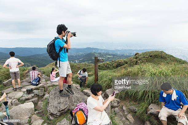 A group of people taking pictures on the top of the yangmingshan mountain in Taipei Taiwan