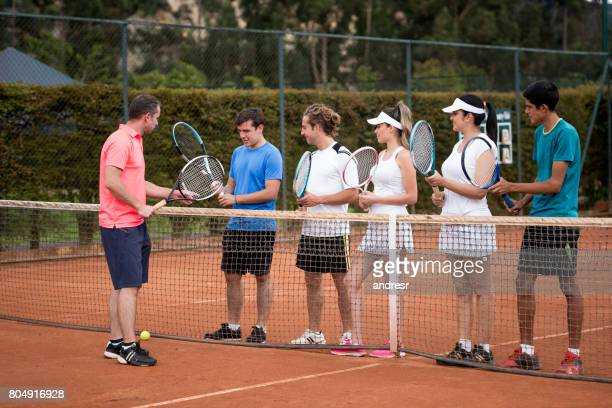 Group of people taking tennis lessons