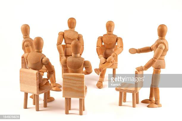 group of people talking about - wooden mannequins in circle