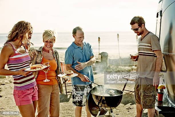 A group of people talking and laughing near a BBQ.