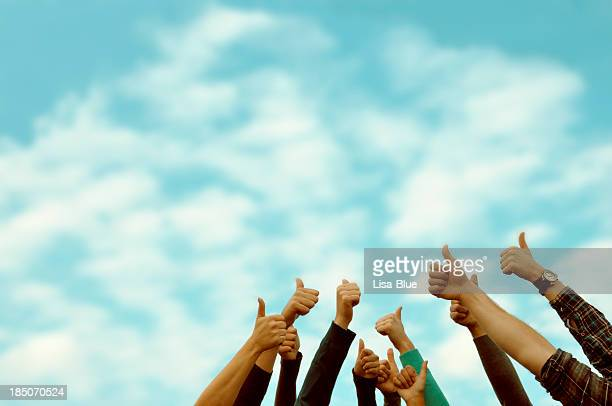Group of people thumbs up blue sky