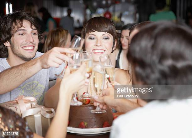 Group of people toasting and smiling at a birthday party in a restaurant