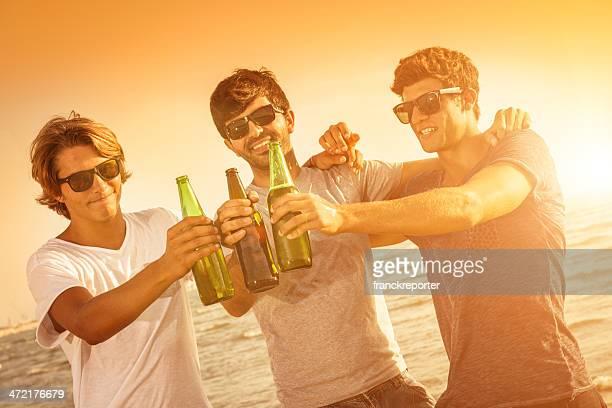 Groupe de personnes portant un toast au coucher du soleil avec des bières