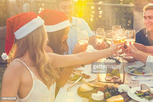 Group of people toasting with Santa hats.