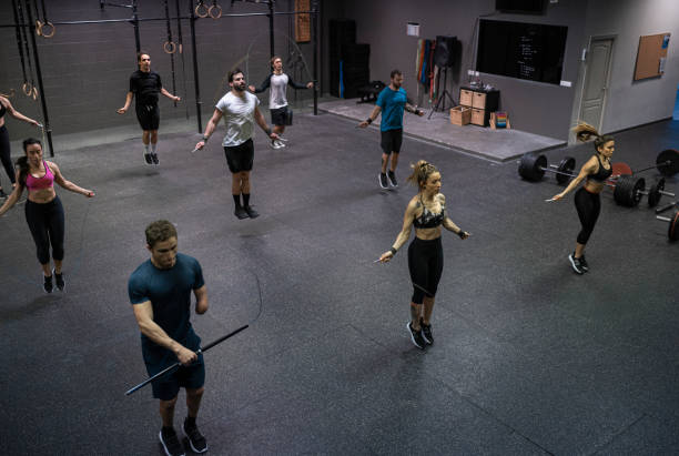 Group of people training with jumping rope in gym
