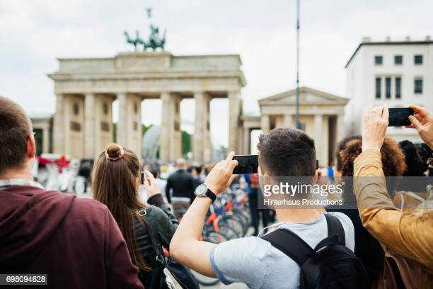 group of people travelling together take pictures of brandenburg gate - tourist stock-fotos und bilder