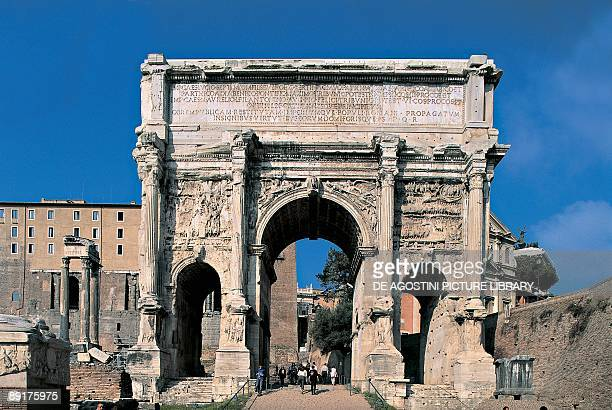 Group of people under an archway Arch Of Septimus Severus Roman Forum Rome Lazio Italy