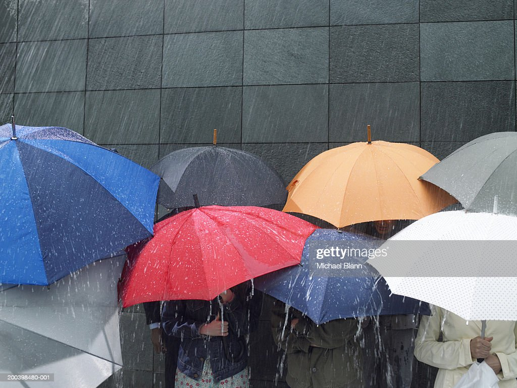 Group of people under umbrellas in rain : Stock Photo