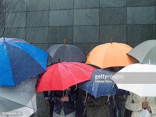 group of people under umbrellas in rain - umbrella stock pictures, royalty-free photos & images