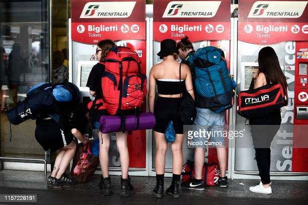 Group of people use automatic machines to buy train tickets. On 22 July 2019 an arson fire in a rail transformer room near Florence caused long...