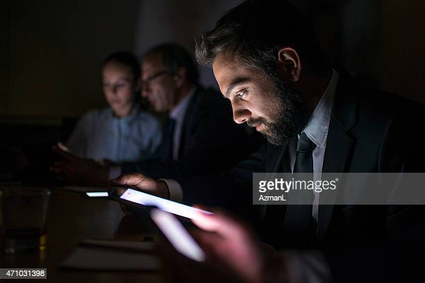 Group of people using devices in a dark room, focused on man