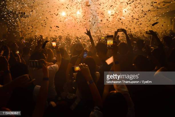group of people using mobile phones at music concert - large group of people stock pictures, royalty-free photos & images