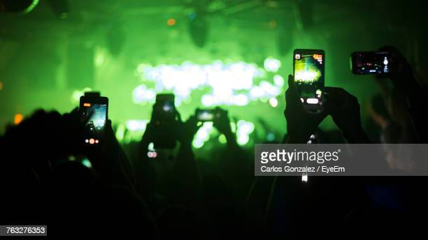 group of people using smart phone at music concert - filming stock pictures, royalty-free photos & images