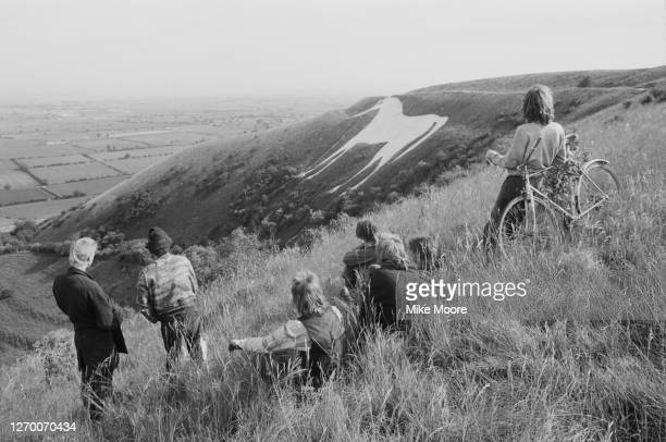 Group of people viewing the Westbury White Horse, an ancient hill figure on the escarpment of Salisbury Plain, from Bratton Downs in Wiltshire, UK,...