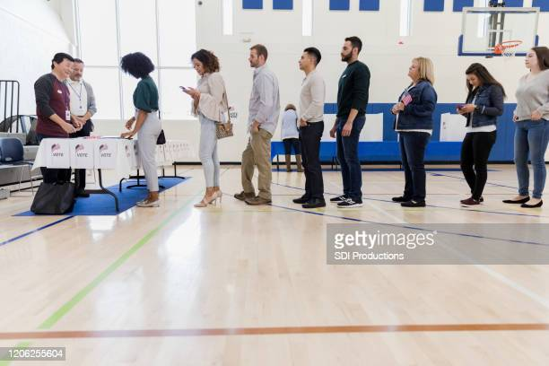 group of people wait in long line in polling place - polling station stock pictures, royalty-free photos & images