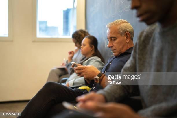 groep mensen te wachten voor sollicitatiegesprek met inbegrip van een speciale persoon - werkloosheid stockfoto's en -beelden