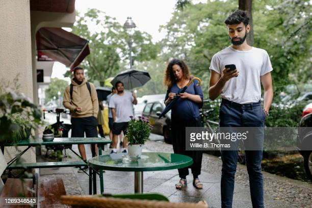 group of people waiting in line to enter restaurant - lining up stock pictures, royalty-free photos & images