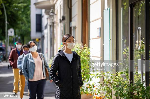 group of people waiting in social distance outside a pharmacy - essential workers stock pictures, royalty-free photos & images