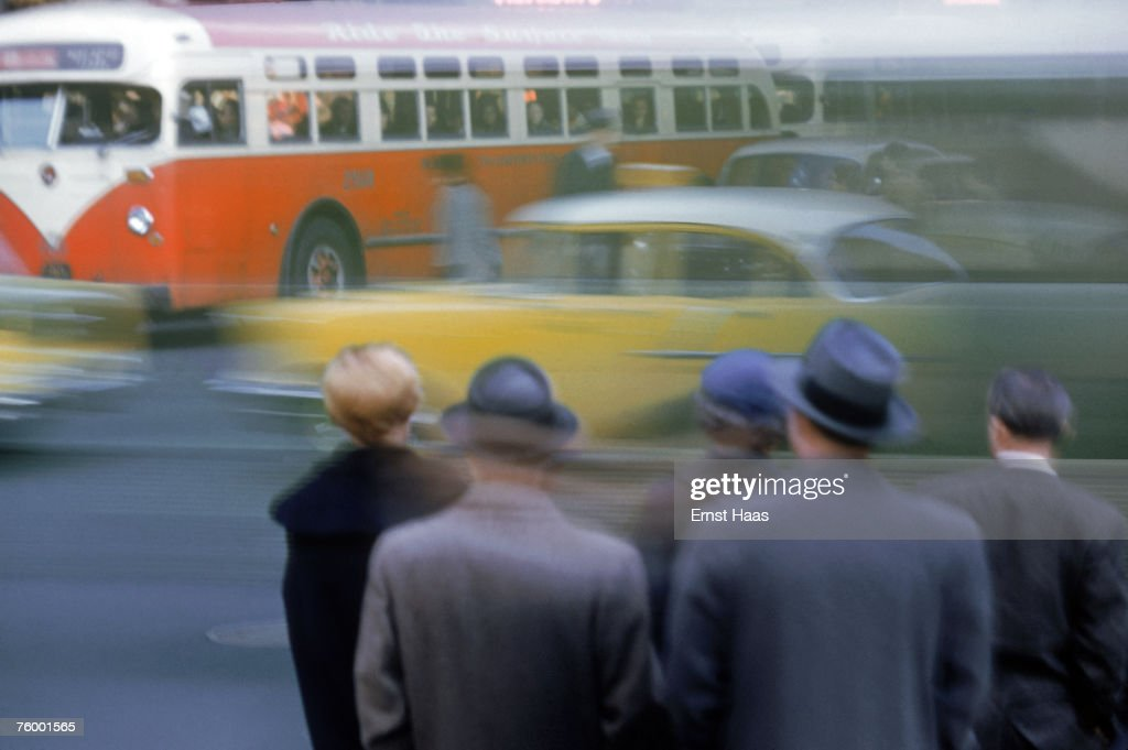 A group of people waiting to cross a busy road in New York City, 1953.