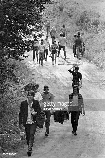 Group of people walk down the road at the Woodstock Music Festival, Bethel, NY, August 15, 1969.