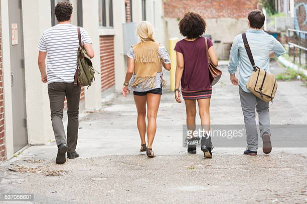group of people walking away - black alley stock photos and pictures