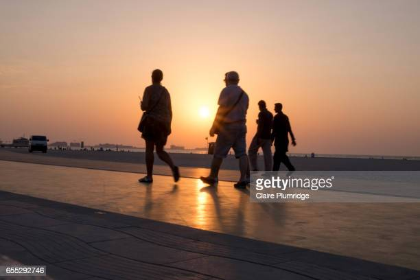 Group of people walking on a purpose built walking/running track on a beach in Dubai at sunset