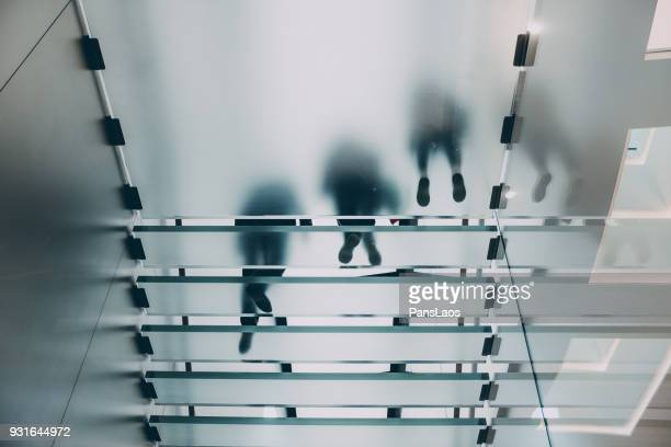 group of people walking on glass staircase - man made structure stock pictures, royalty-free photos & images