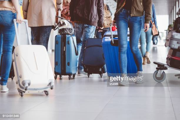 Group of people walking with suitcase at airport terminal