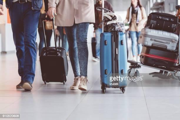 group of people walking with suitcase at airport terminal - izusek imagens e fotografias de stock