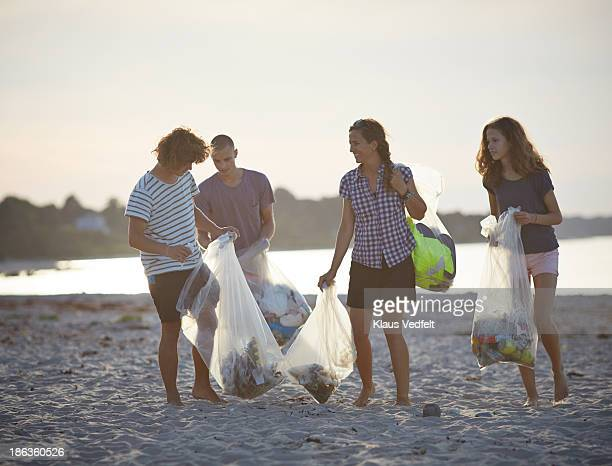 Group of people walking with trashbags on beach
