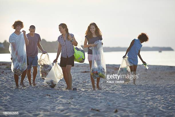 group of people walking with trashbags on beach - levantando - fotografias e filmes do acervo