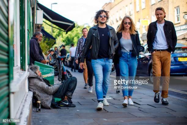 A group of people walks past homeless people on Broadway Market in east London on July 23 2017 / AFP PHOTO / Tolga Akmen