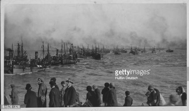 A group of people watch a fishing fleet return to harbor