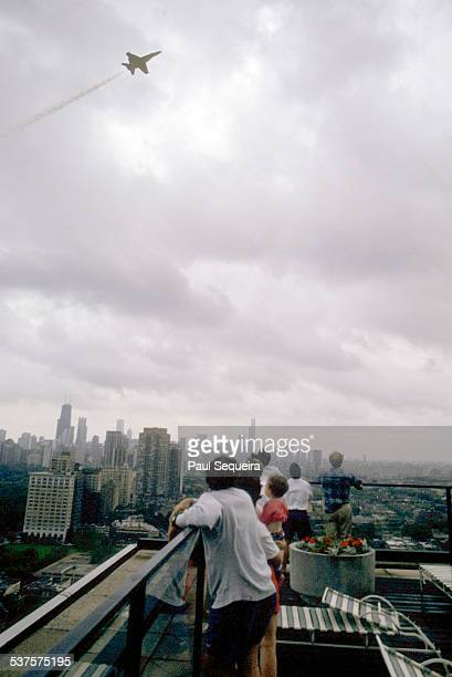 A group of people watch as a jet streaks across the sky as part of the Chicago Air and Water Show Chicago Illinois 1980s Downtown Chicago is visible...