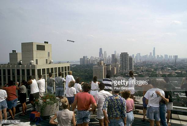 A group of people watch as four jets perform precision stunts as part of the Chicago Air and Water Show Chicago Illinois 1980s Downtown Chicago is...