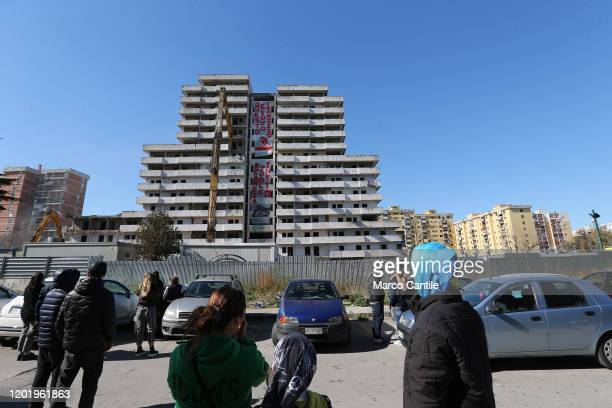 A group of people watch the demolition of the building known as Vela Verde in the Scampia district of Naples The building is the first of other...
