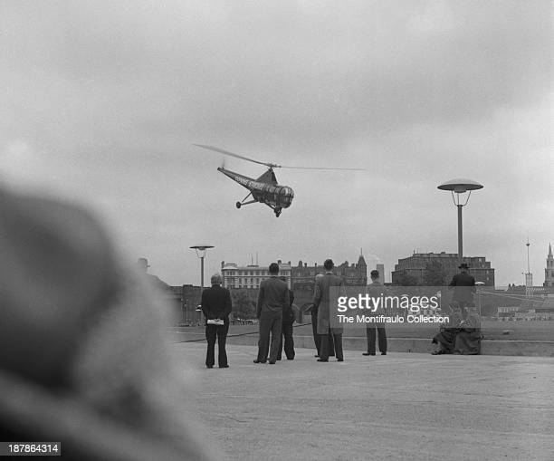 Group of people watching an Evening Standard helicopter coming into land, London, England circa 1950.