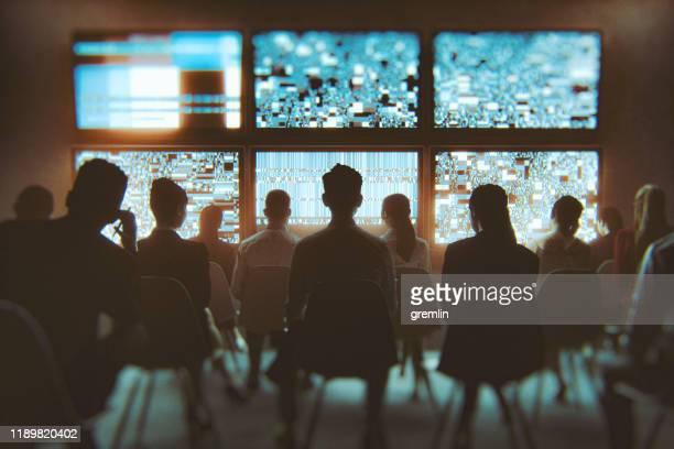 groep mensen die meerdere tv-toestellen tegelijk bekijken - de media stockfoto's en -beelden