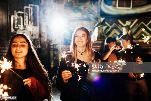 Group Of People Waving Sparklers While Dancing At Colourful Nightclub