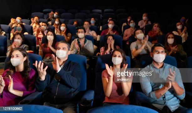 劇場で拍手しながらフェイスマスクを着用した人々のグループ - performance group ストックフォトと画像