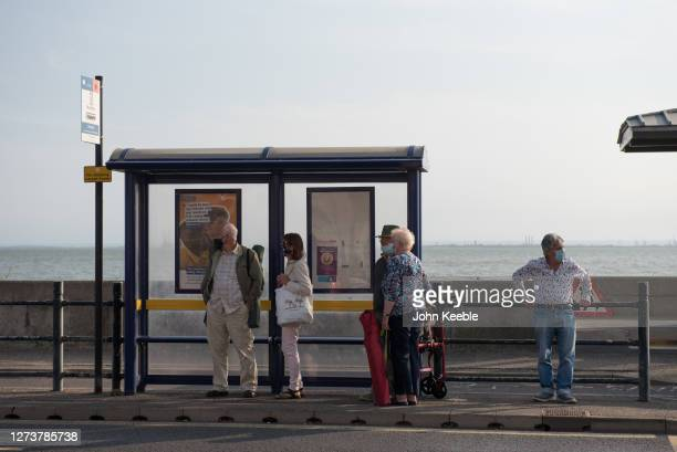 A group of people wearing face masks wait for a bus at the bus stop on September 20 2020 in Southend on Sea London