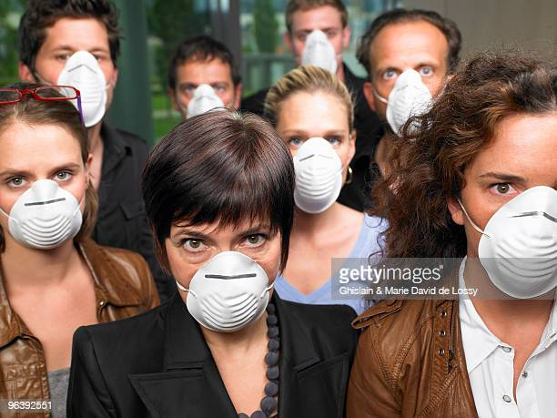 group of people wearing protection masks - epidemia fotografías e imágenes de stock