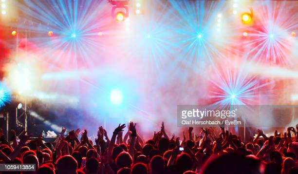 group of people with arms raised at music concert - stage light stock pictures, royalty-free photos & images