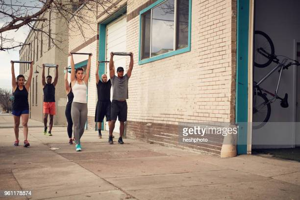 group of people with arms raised carrying weights equipment, front view - heshphoto fotografías e imágenes de stock